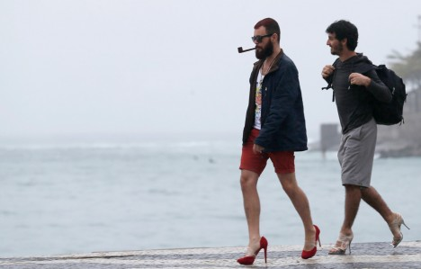 Image: Men wearing high heeled shoes walk in front of Copacabana beach during what they said was 'an artistic' protest ahead of Pope Francis' visit to the beach in Rio de Janeiro