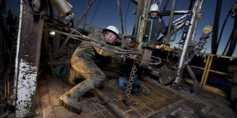 Canada, Alberta, Oil workers using oil drill