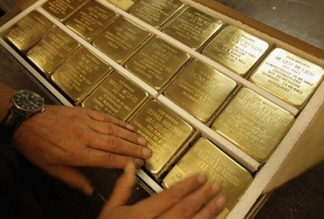 A worker prepares finished Stolpersteine, which are concrete cobblestones afixed with a brass commemorative plaque, for shipping at the Stolpersteine manufacturing studio on August 10, 2012 in Berlin, Germany. The Stolpersteine project, launched by German artist Gunter Demnig in 1995, commemorates victims of the Holocaust. Demnig installs the stones into the sidewalk at the front entrance of the residence where the victim last lived before being deported by the Nazis. Demnig has installed over 30,000 stones all across Europe at the request of families of victims or local authorities. Stolpersteine literally translates to