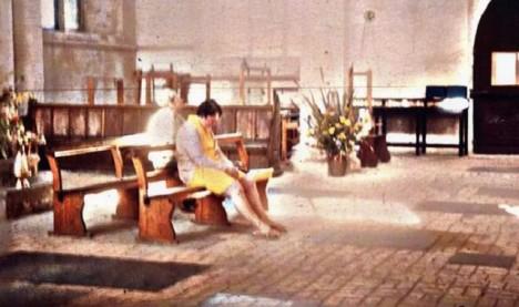 Fotografie Diane v kostele, za kterou sedí zvláštní bílá postava s čepcem na hlavě.