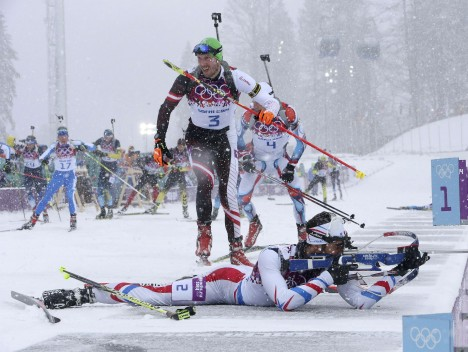 France's Martin Fourcade (bottom) shoots as Austria's Dominik Landertinger (C) leaves the shooting range during the men's biathlon 15km mass start event at the Sochi 2014 Winter Olympics in Rosa Khutor February 18, 2014.     REUTERS/Sergei Karpukhin (RUSSIA - Tags: SPORT BIATHLON OLYMPICS TPX IMAGES OF THE DAY)    ATTENTION EDITORS: PICTURE 04 OF 20 FOR PACKAGE 'SOCHI - EDITOR'S CHOICE'  TO FIND ALL SEARCH 'EDITOR'S CHOICE - 18 FEBRUARY 2014' ORG XMIT: PXP04
