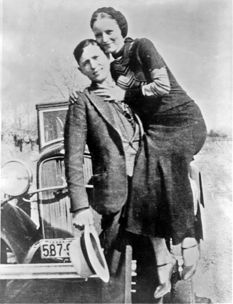 Bonnie Parker and Clyde Barrow, sometime between 1932 and 1934, when their exploits in Arkansas included murder, robbery, and kidnapping. Contrary to popular belief the two never married. They were in a long standing relationship. Posing in front of an early 1930s Ford V-8 automobile. Date between 1932 and 1934