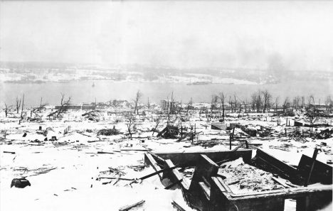 A view across the devastated neighbourhood of Richmond in Halifax, Nova Scotia after the Halifax Explosion, looking toward the Dartmouth side of the harbour. The steamship Imo, one of the ships in the collision that triggered the explosion can be seen aground on the far side of the harbour - Halifax after 6th December 1917.