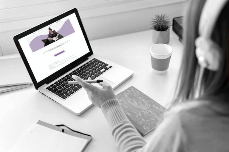 mujer sentada mirando la pantalla de su portatil donde se ve la web de épsilon psicología