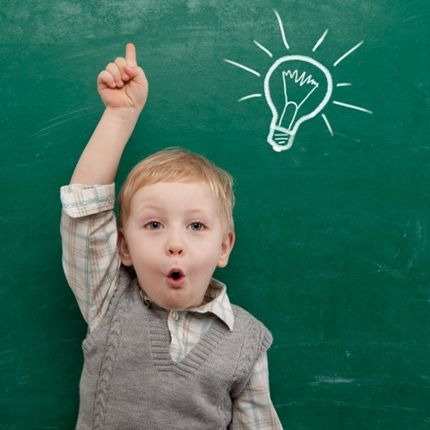 Boy in front of blackboard having an idea