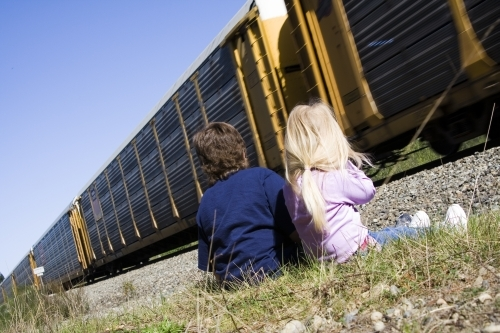 Children enjoy a passing train on a warm sunny afteroon.
