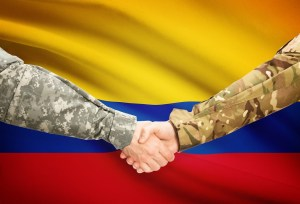 Men in uniform shaking hands with flag on background - Colombia