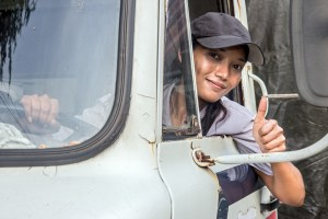 Woman truck driver looking out the window with thumb up gesture