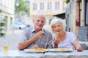 Two eldery people eating chips