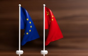 China and European Union miniature flags on wooden background. 3d illustration