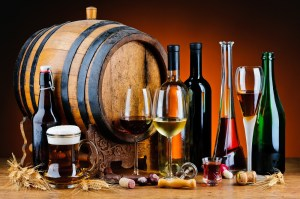 still life with different alcoholic drinks and wooden barrel