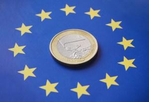 1 euro coin on top of the European flag, finance concept