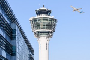 Munich international airport control tower and terminal modern buildings with departing taking off plane