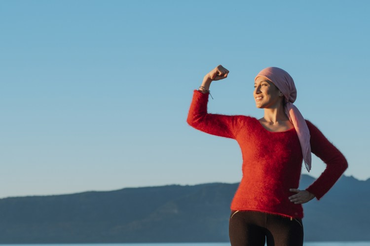 Medical and health concept. Healthy woman showing her fist of power against female cancer in the background of the blue sky. She wears a pink scarf and a red sweater.
