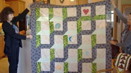 Mary Birrell and Terry hold up Mary's quilt.