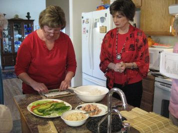 Betsy demonstrates the fine art of sushi making while Maureen Callaway is an attentive student.