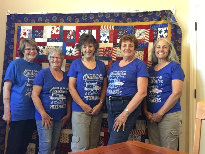 Piecemakers with their new T-shirts in front of the Quilt of Valor top.