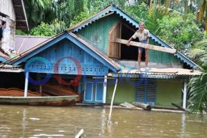 BUAT PANGGAUAN. Salah seorang warga Dusun Lubuk Lagak, Desa Lubuk Dagang, Kecamatan Sambas, membuat panggauan di dekat atap rumahnya yang telah dimasuki air semeter, Kamis (11/2). M. Ridho-Rakyat Kalbar