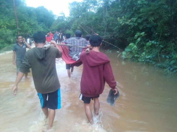 DITANDU. Salah seorang warga yang sakit terpaksa ditandu lantaran akses jalan menuju Desa Semabi Kecamatan Sekadau Hilir Kabupaten Sekadau rusak tak bisa dilewati kendaraan, Jumat (2/3). Dok