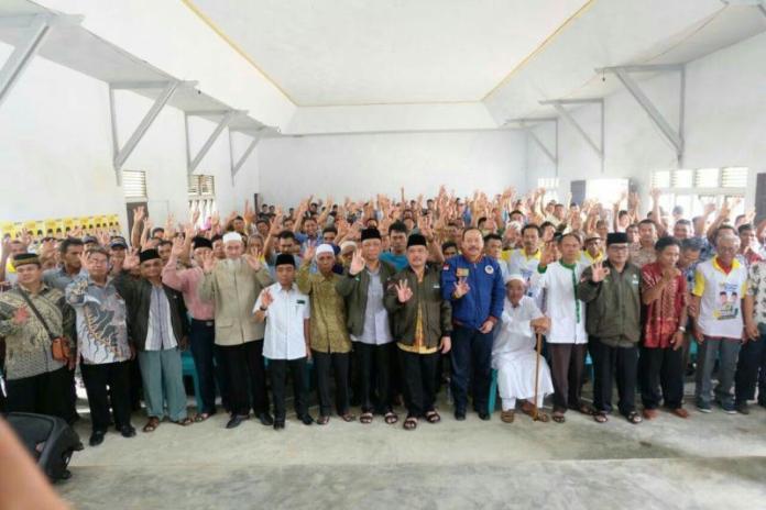 TIGA JARI. Sutarmidji-Ria Norsan bersama masyarakat memberikan kode tiga jari yang merupakan nomor urut dari pasangan Midji-Norsan di Kecamatan Sokan Kabupaten Melawi, Senin (12/3). Kang Enchus for RK
