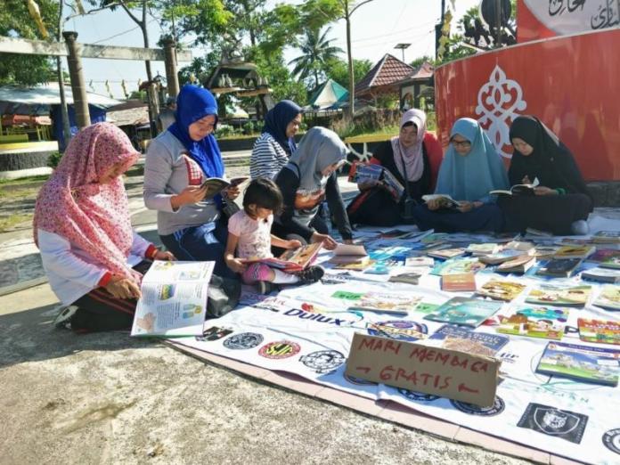 ANTUSIAS. Masyarakat dengan antusias membaca buku yang digelar Komunitas Membaca dan Perpustakaan Jalanan Singkawang di Jalan Merdeka, Singkawang, Minggu (22/7)—SUHENDRA/RK