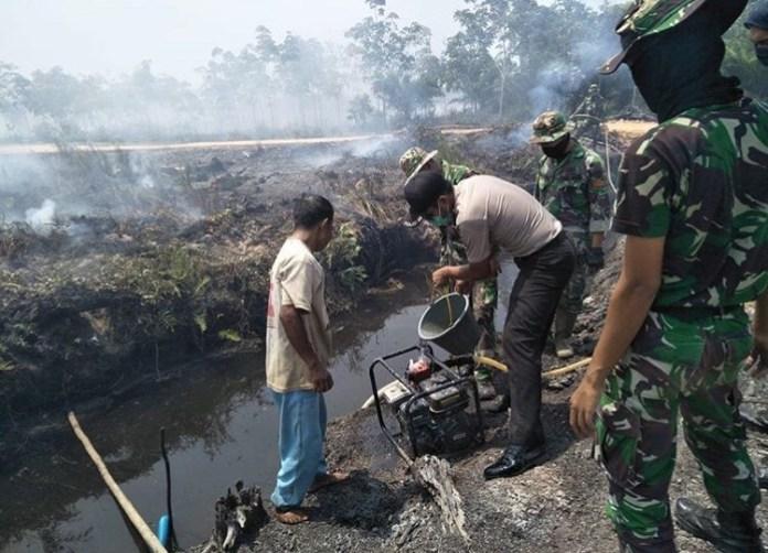 PADAMKAN API. Personel Polres, TNI dan BPBD bahu-membahu bersama masyarakat memadamkan api yang melahap lahan dan hutan di wilayah Kabupaten Mempawah, Senin (20/8).