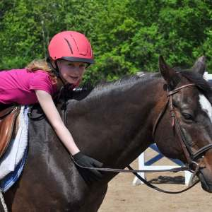 Manes & Tails Camp at Kraus Farms - Girl riding on horse while petting it's neck.