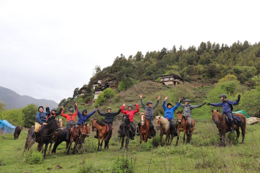 A group riders on Bhutanese ponies in front of a monastry build on a cliff