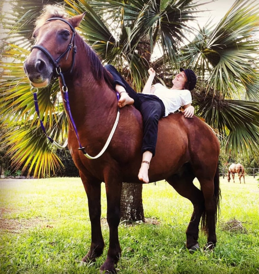 Hebe Webber having a break on horseback under palm trees.