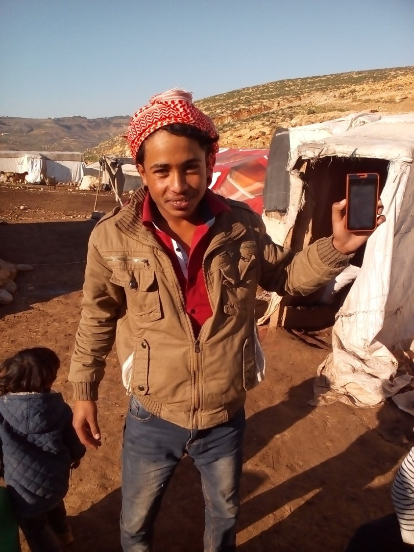 A young Bedouin proudly showing his solar panel