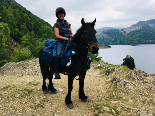 Clare on her Fells pony Pansy with all the saddle bags and gear while horse trekking in England at the shore of Ullswater lake in the Lake District