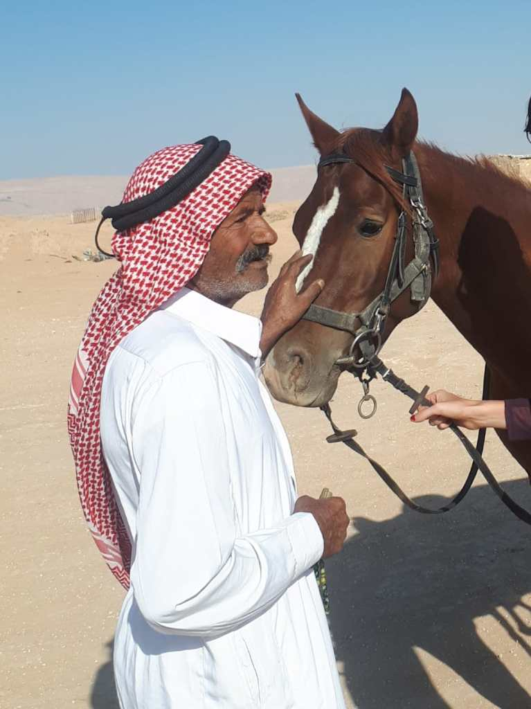 A Bedouin petting an Arabian Horse in Jordan