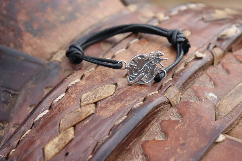 The Black Bracelet presented on a rustic leather saddle