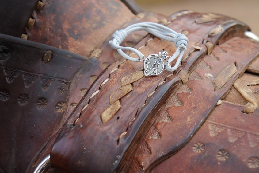 The Silver Equestrian Woman Bracelet shown on a rustic saddle