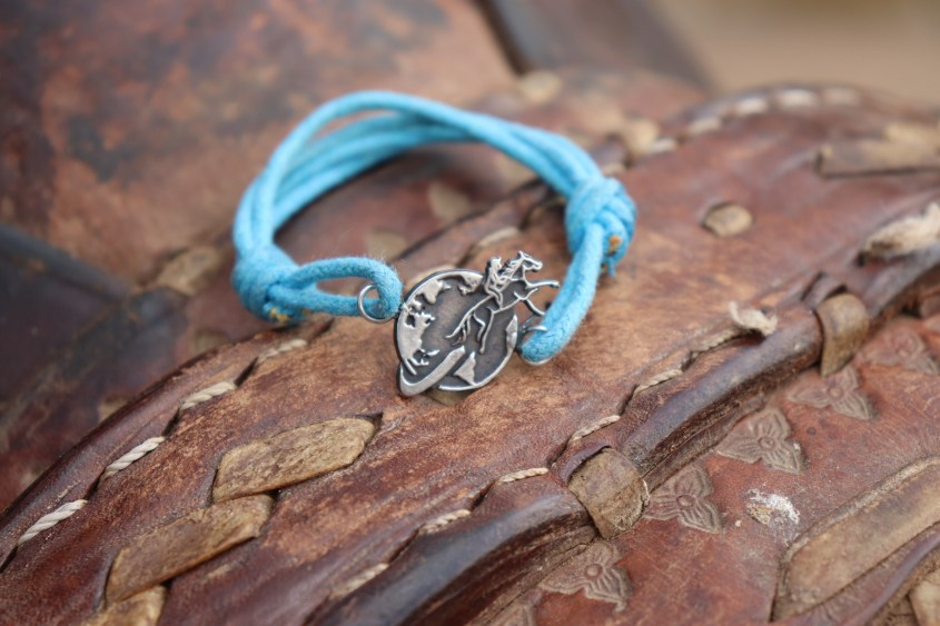 The Lighting Blue Equestrian Woman Bracelet resting on a traditional leather saddle