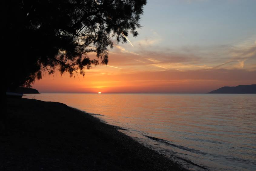 A beautiful sunset in the sea with Lesvos to the left and Turkey to the right.