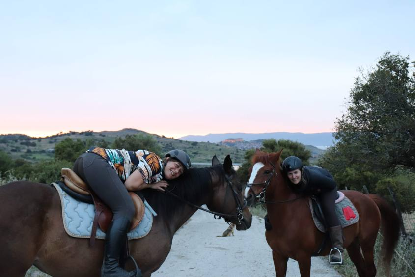 Two women who love horses, travel and adventure don't want to stop riding horses in Greece and hug them.