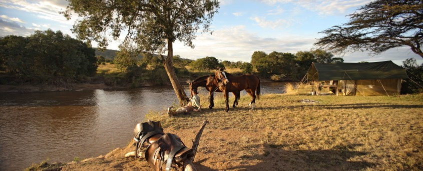 Felicia and Gordie are relaxing on the riverside with their two horses. Their camp in the background is in the perfect spot