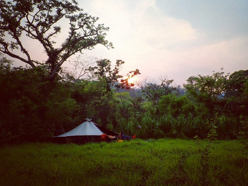 """The community tent """"Big Daddy"""" set up in a picturesque spot in a grassy field"""