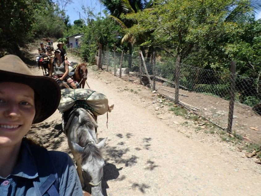 A selfie taken on horseback on a hot and long riding day. In the background you can see the rest of the horse caravan traveling through Guatemala