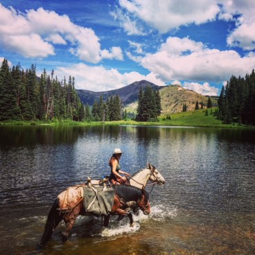 crossing water while leading a packhorse on a trek through the Rocky Mountains in Colorado on horseback
