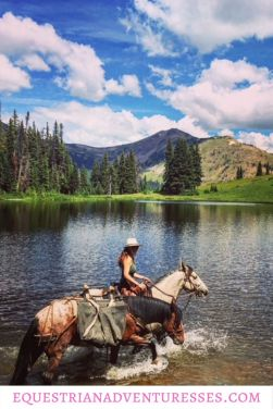 Adrienne crossing trough water on a horse riding trek with a packhorse through the Rocky Mountains in Colorado