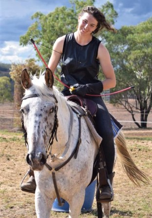 After a successful horse archery trial, Odessa is looking proudly at the mare she's riding.