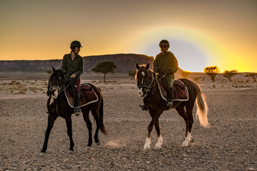 Two women are riding Arabian horses in the desert in Morocco