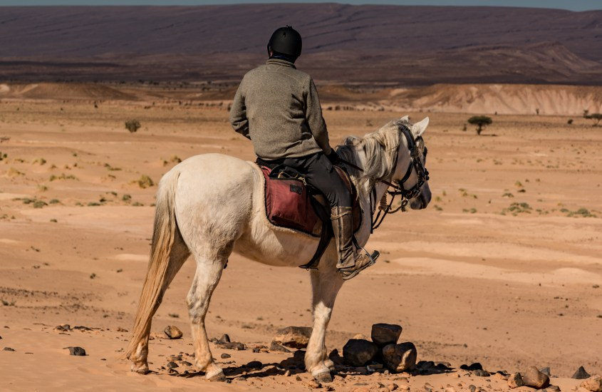 "A man riding his trusty Arabian steed ""Atlas"" in Morocco"