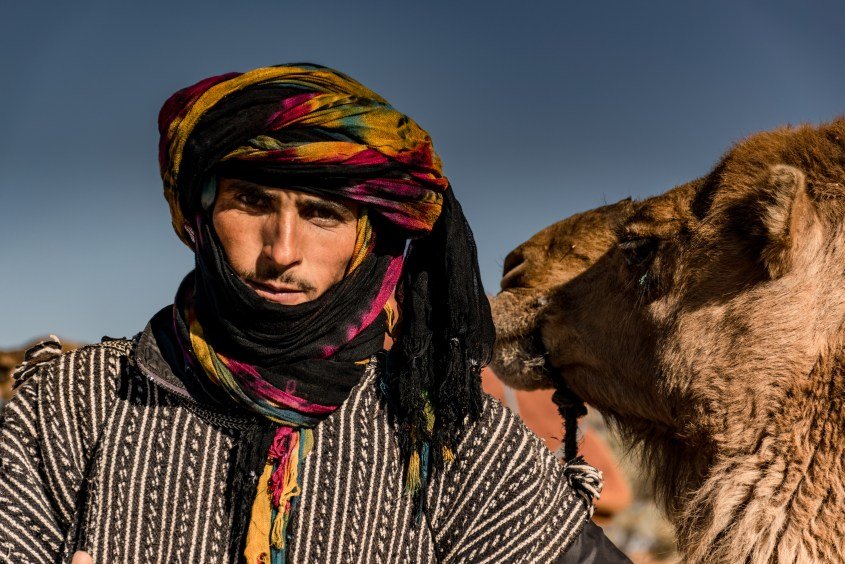"A Moroccan man wearing a ""shesh"", the traditional Touareg turban, standing beside one of his camels"
