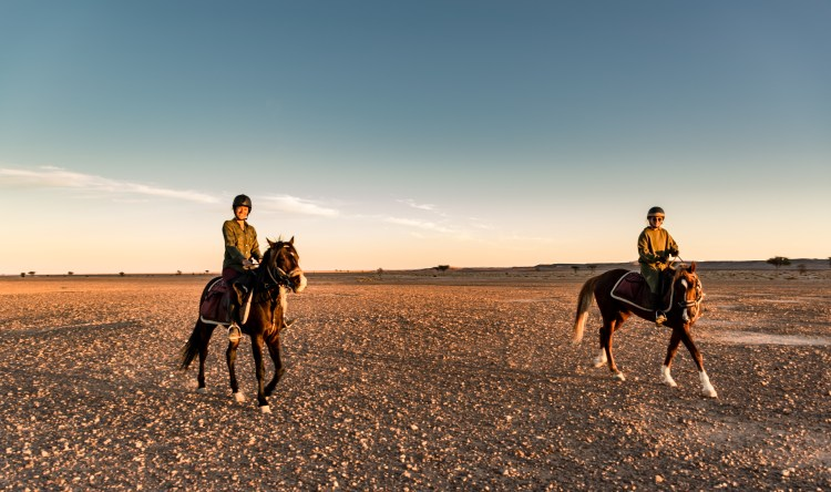 Two sisters are riding Arabian Horses with big smiles on their faces.