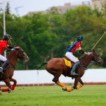 Two women polo players chasing the ball down the polo field in a polo tournament