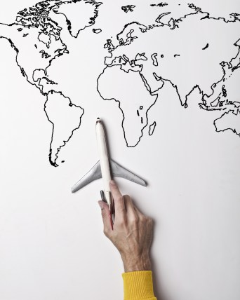 Someone holds a toy plane against a map of the world