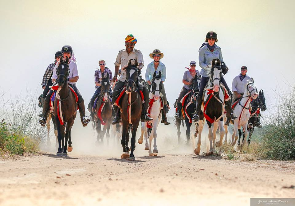 A group of tourists and their guides enjoy a canter on their horse riding adventure in India